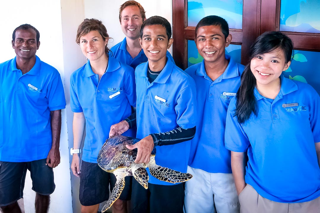 Nao the rescued Hawksbill turtle poses with Seamarc staff at Kuda Huraa's Marine Discovery Centre